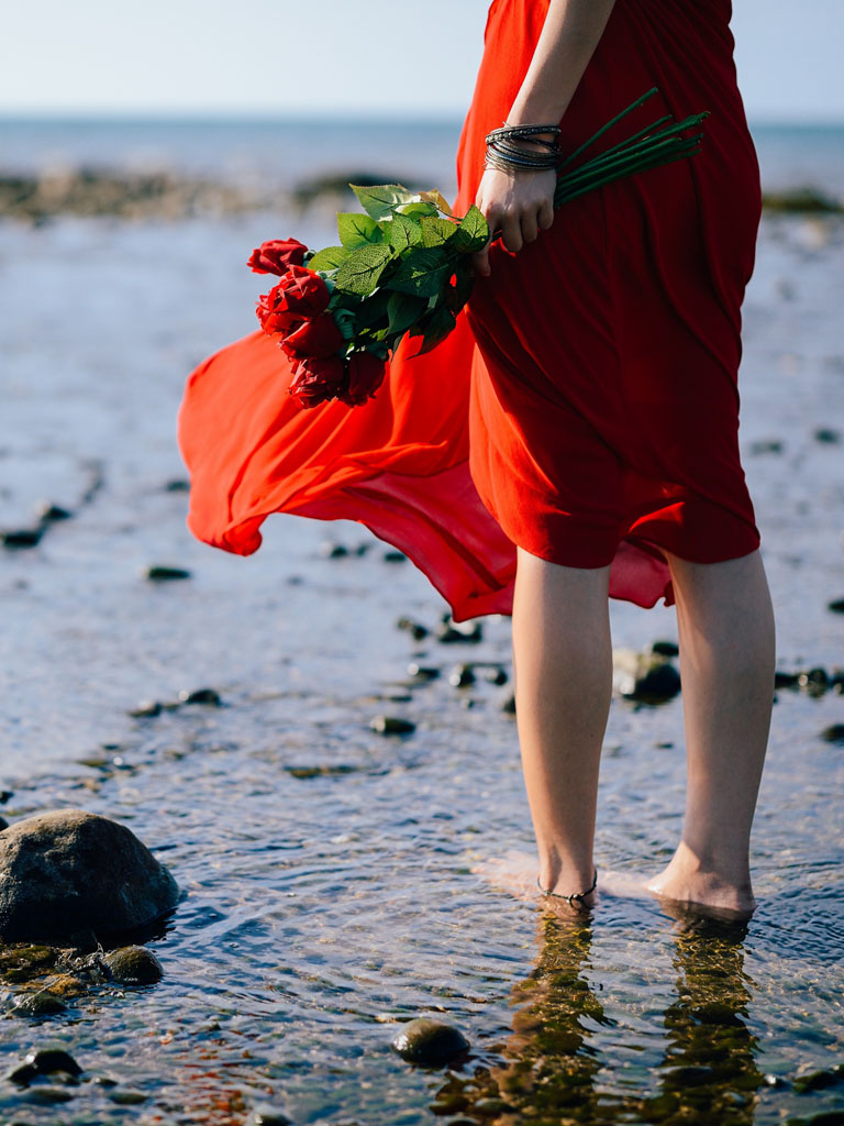 Girl in Red Dress with Red Roses at Beach